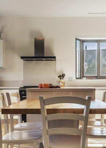 מטבח לבן עם שולחן אוכל במרכז